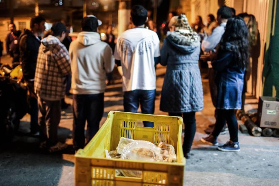 Voluntário rezam em uma rua do Cambuci, zona central de São Paulo, antes de distribuirem sopas para moradores de rua