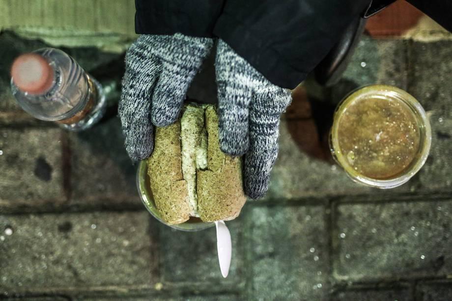 Morador de rua se alimenta com sopa distribuída por voluntários, na região central de São Paulo