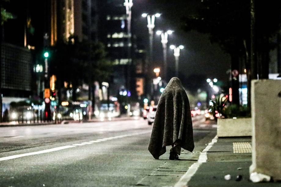 Morador de rua caminha coberto por mantas na Avenida Paulista. Os termômetros chegaram a marcar 7,9º C em São Paulo
