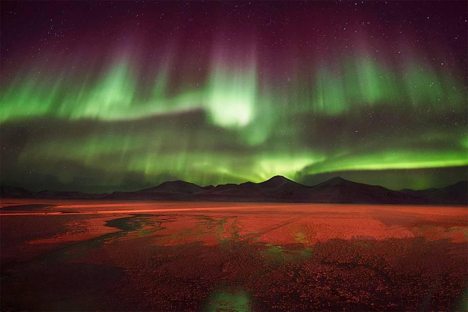 Luzes verdes e roxas de uma aurora boreal iluminando o solo de uma pequena cidade que sobrevive da mineração de carvão, no arquipélago de Svalbard, na Noruega.