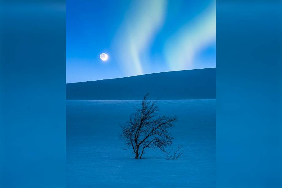 Lua crescente e Marte fotografados sobre o solo coberto de neve da cordilheira de<span>Saltfjellet, na Noruega. A aurora boreal apareceu de surpresa na imagem, segundo o fotógrafo.</span>