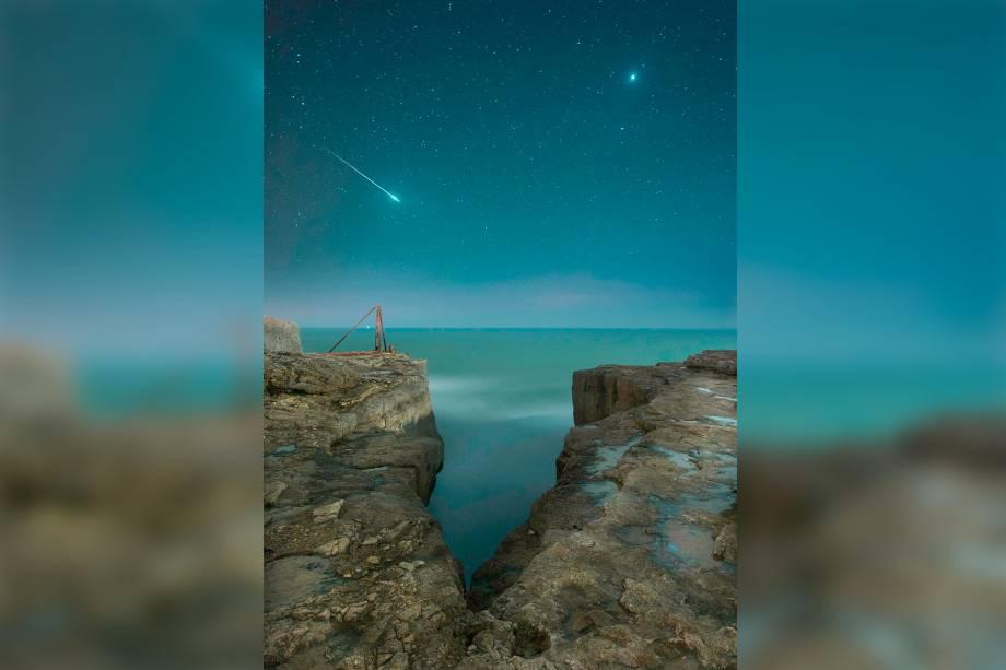 Estrela cadente atravessa o céu entre a fenda de um precipício em Portland, uma ilha na Inglaterra, enquanto nosso planeta vizinho, Vênus, aparece atrás.