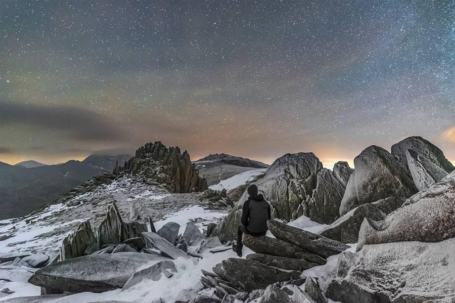 Observador solitário observando o céu estrelado em uma manhã fria no topo do Castelo dos Ventos, na montanha<span>Glyder Fach, no País de Gales. Para tirar essa foto, o fotógrafo montou seu equipamento e aguardou cerca de 15 horas no escuro, a -10ºC. Os 20 minutos em que o céu clareou foram suficientes para registrar a imagem.</span>