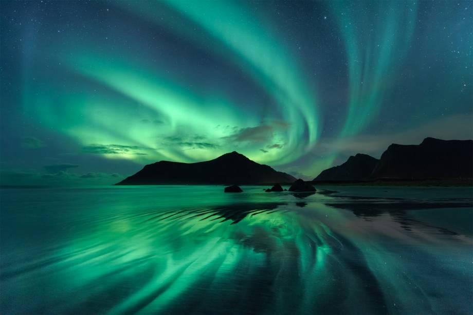 Luzes de uma aurora boreal criam um espelho d'água em <span> Skagsanden,</span>uma praia na Noruega. Para tirar a foto, o fotógrafo teve de esperar o nível da água abaixar.