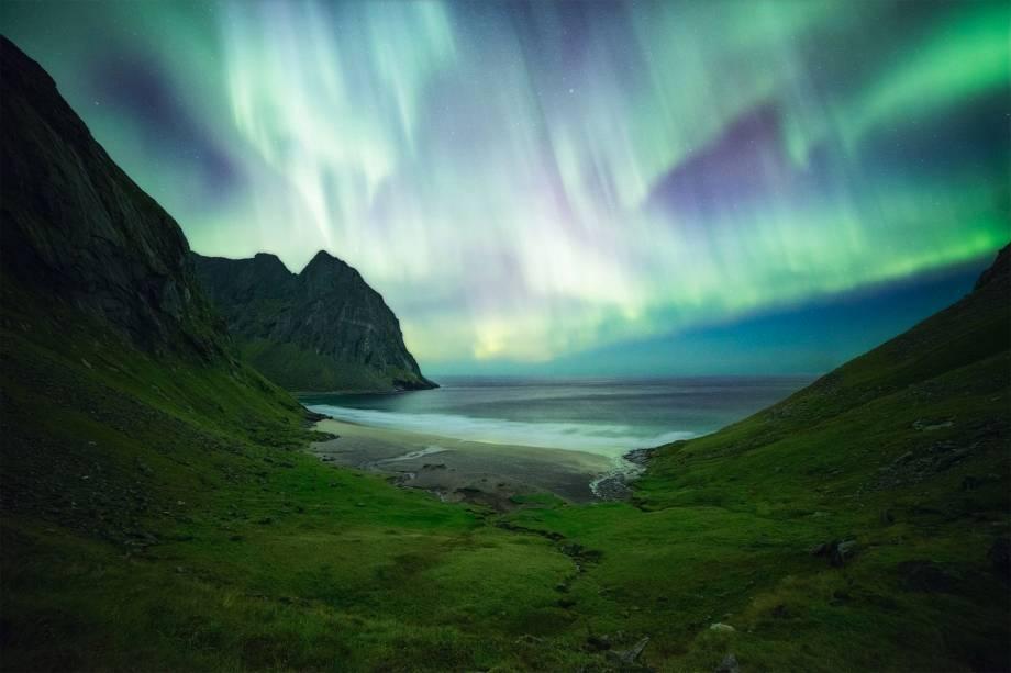 Aurora boreal retratada durante uma longa caminhada até uma praia em Lofoten, um arquipélago de ilhas na Noruega. A foto foi tirada por volta da meia noite.