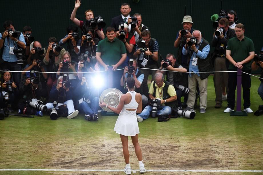 Tenista Garbine Muguruza, da Espanha, posa com o troféu do torneio de Wimbledon, após vencer a americana Venus Williams na final, em Londres