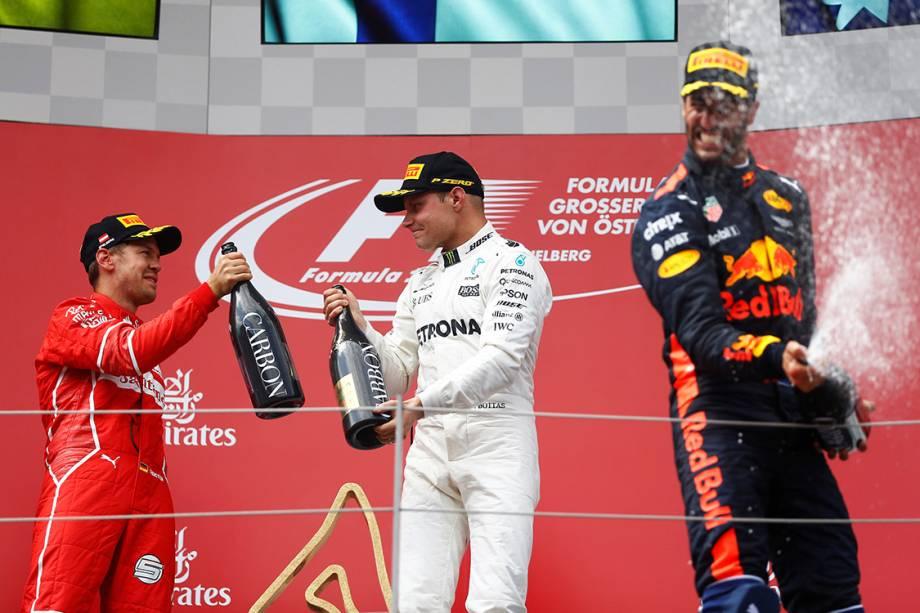 O finlandês Valtteri Bottas, da Mercedes, comemora no pódio com Sebastian Vettel, da Ferrari, e Daniel Ricciardo, da Red Bull Racing, após vencer o GP da Áustria