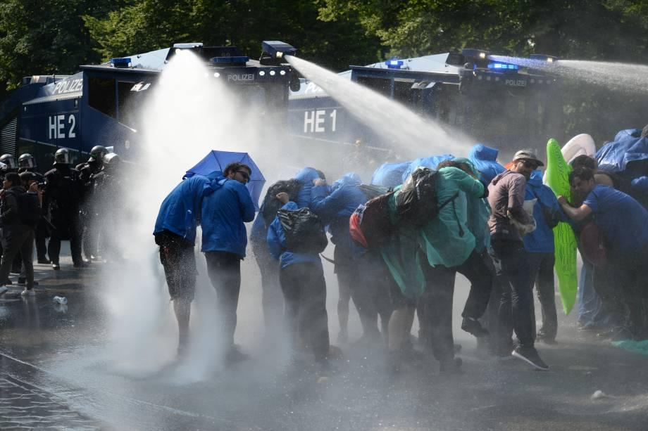 Manifestantes são atingidos por jatos de água de caminhões da policia alemã na tentativa de dispersar os protestos contra a conferência do G20, em Hamburgo.