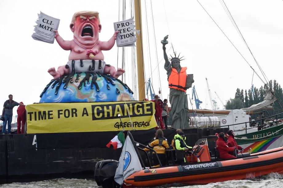 Ativistas do Greenpeace manifestam contra a conferência do G20 ao lado de uma estátua do presidente norte americano Donald Trump.