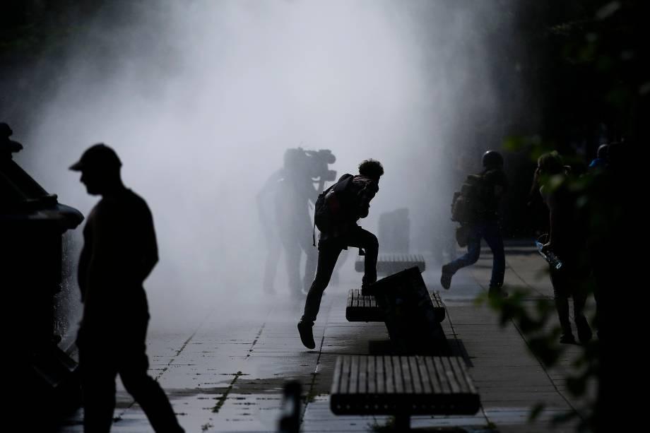 Manifestantes se dispersam ao serem atingidos por jatos de água dos caminhões da polícia alemã durante protesto contra a conferência do G20 em Hamburgo, na Alemanha.