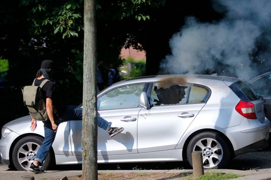 Manifestante chuta um carro durante protesto contra a conferência do G20 na Alemanha.