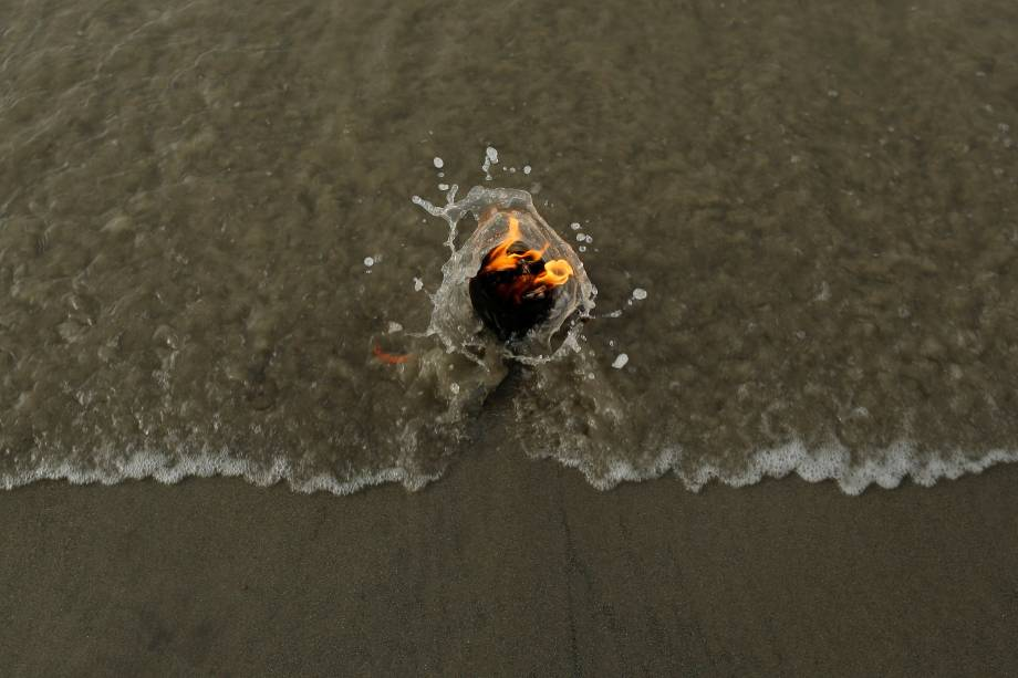 Uma lamparina acesa por um peregrino hindu é vista na confluência do rio Ganges e da Baía de Bengala, na Ilha de Sagar, ao sul de Kolkata, Índia.