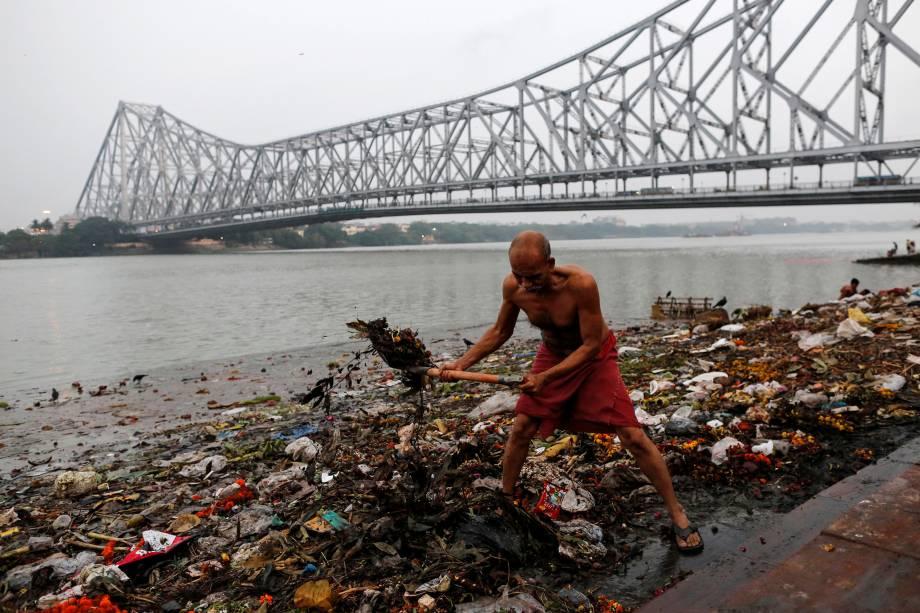 Um homem limpa o lixo ao longo das margens do rio Ganges em Kolkata na Índia.