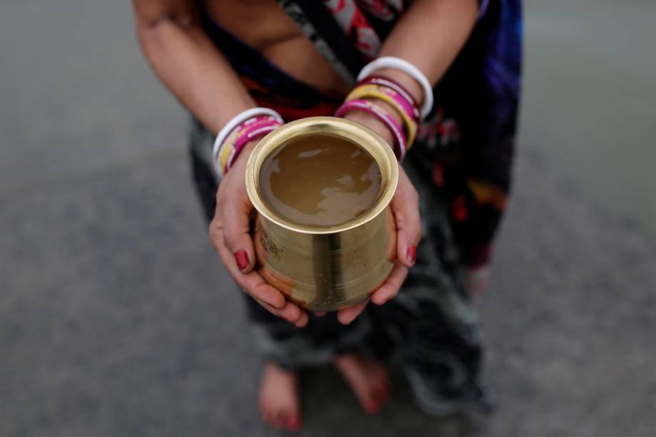 Devoto hindu segura um recipiente com a água turva do Rio Ganges, em Kolkata na Índia.