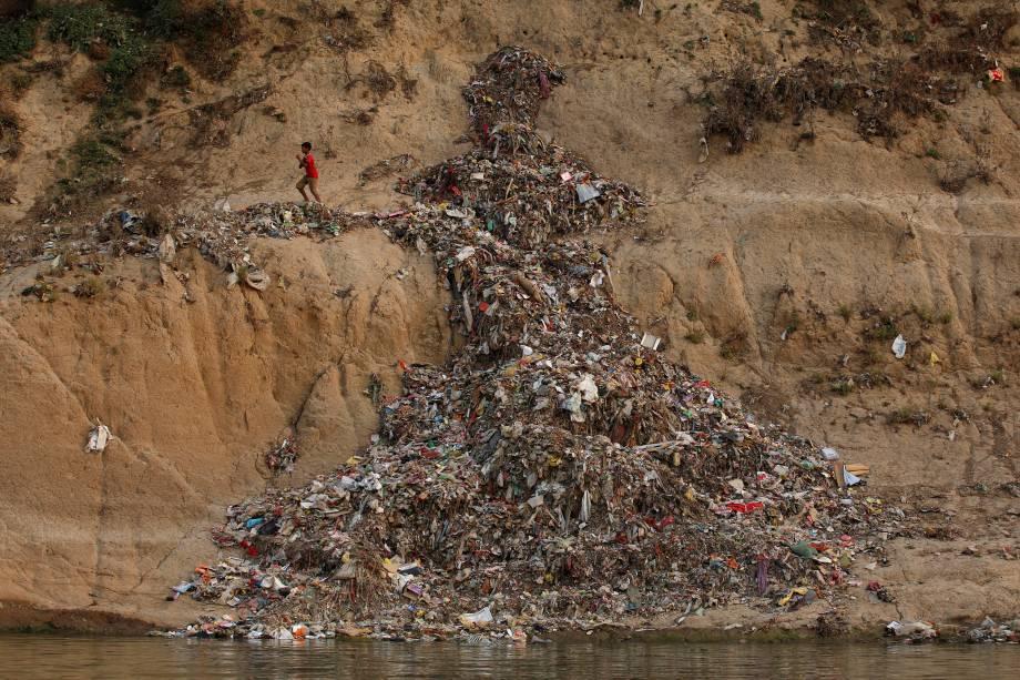 Um menino indiano atravessa uma pilha de lixo ao longo do rio Ganges em Mirzapur.