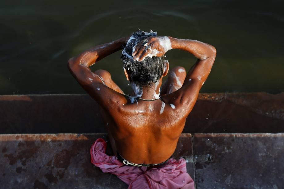 Um homem toma banho nas margens do rio Ganges, em Varanasi na Índia.