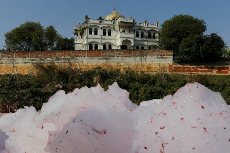Camadas de espuma bóiam na superfície em um dreno de esgoto que flui para o rio Ganges em Kanpur, na Índia.