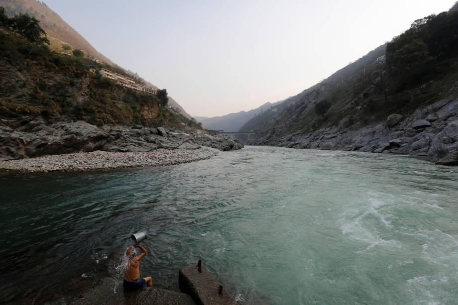 Um devoto hindu se banha na confluência dos rios Alaknanda e Bhagirathi, que formam o Ganges em Devprayag, na Índia.