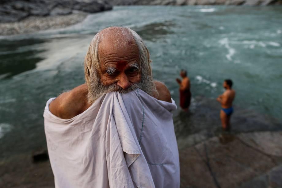Um devoto hindu se enrola em suas roupas após um mergulho no rio Ganges em Devprayag na índia.