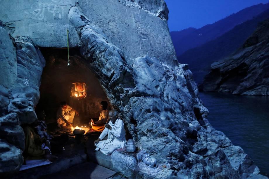 Sacerdotes hindus sentam-se dentro de uma caverna enquanto realizam preces noturnas às margens do rio Ganges em Devprayag, na Índia