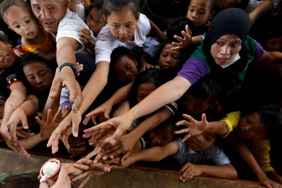 Pessoas se esforçam para alcançar um sorvete em um campo de evacuação fora da cidade, enquanto tropas do exército continuam seu ataque contra insurgentes do grupo Maute na cidade de Marawi, Filipinas - 05/07/2017
