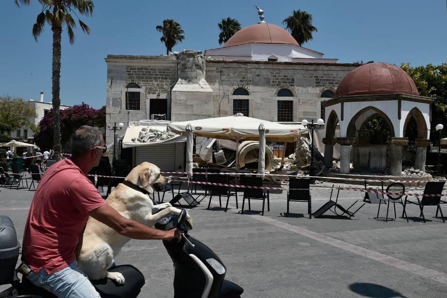 Um homem com seu cachorro passa por uma mesquita destruída em uma praça da ilha grega de Kos, após um terremoto de 6,7 graus que atingiu a Grécia e a estância turca de Bodrum, matando duas pessoas e deixando dúzias de feridos - 21/07/2017