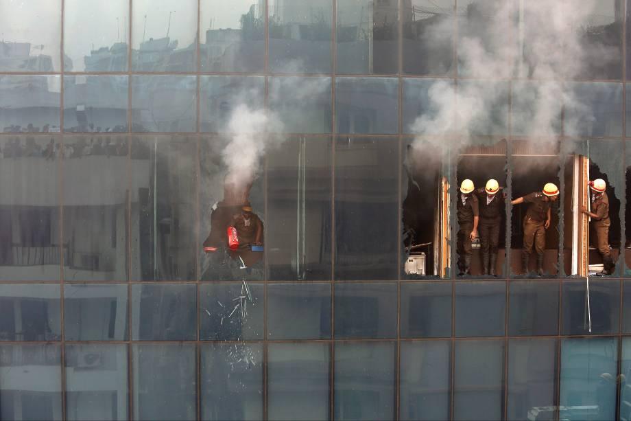 Um bombeiro quebra uma janela de vidro em um prédio de escritórios com um extintor após incêndio em Kolkata, na Índia - 20/07/2017