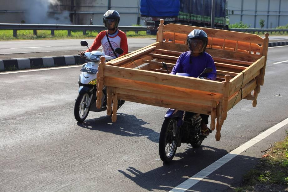 Um vendedor de rua montado em sua motocicleta carrega uma cama de madeira, tentando encontrar clientes na aldeia de Kartasura, em Surakarta, na Indonésia - 20/07/2017
