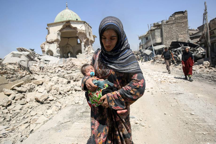 Uma iraquiana, que leva um bebê, caminha pela mesquita destruída de Al-Nuri enquanto foge da Cidade Velha de Mosul, durante a ofensiva das forças do governo iraquiano para retomar a cidade dos combatentes do grupo islâmico - 05/07/2017