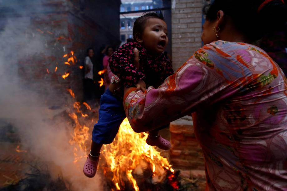 Uma mulher balança uma criança em torno do fogo, onde uma representação do demônio Ghantakarna foi queimada para simbolizar a destruição do mal, durante o festival de Ghantakarna na antiga cidade de Bhaktapur, Nepal - 21/07/2017