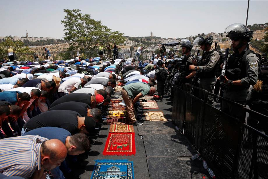 Fiéis palestinos rezam de frente aos policiais israelenses em uma rua perto de um bloco de estradas fora da cidade velha de Jerusalém - 21/07/2017