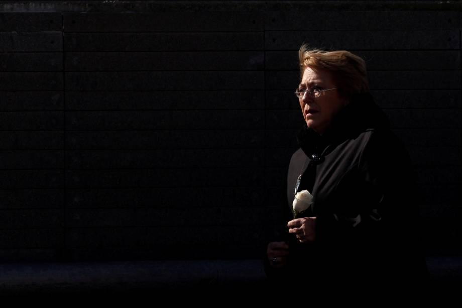 A presidente do Chile, Michelle Bachelet, segura uma flor enquanto visita o Memorial Park em Buenos Aires, Argentina.