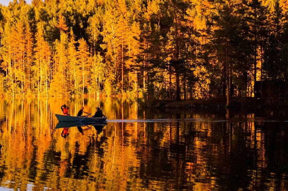 Pessoas sentadas em um barco remando durante o pôr do sol em um lago na cidade de Sortavala, na Rússia - 17/07/2017