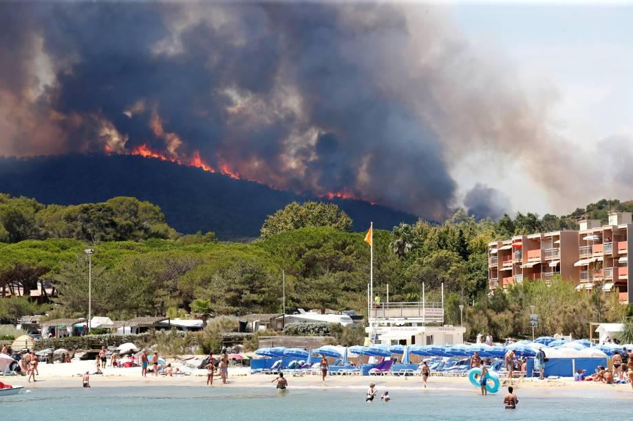 Pessoas se banham na praia em Bormes-les-Mimosas, no departamento de Var, na França, enquanto as chamas do incêndio florestal queimam no alto de uma colina