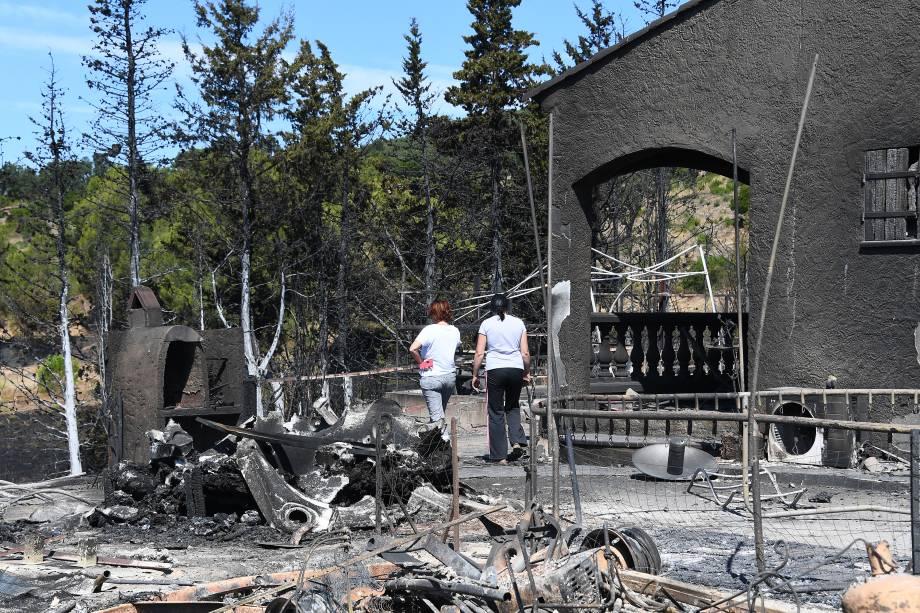 Duas mulheres inspecionam o estrago causado pelo fogo que atingiu sua casa, em Bormes-les-Mimosas, sudeste da França. Cerca de 10 mil pessoas foram obrigadas a deixar suas residências