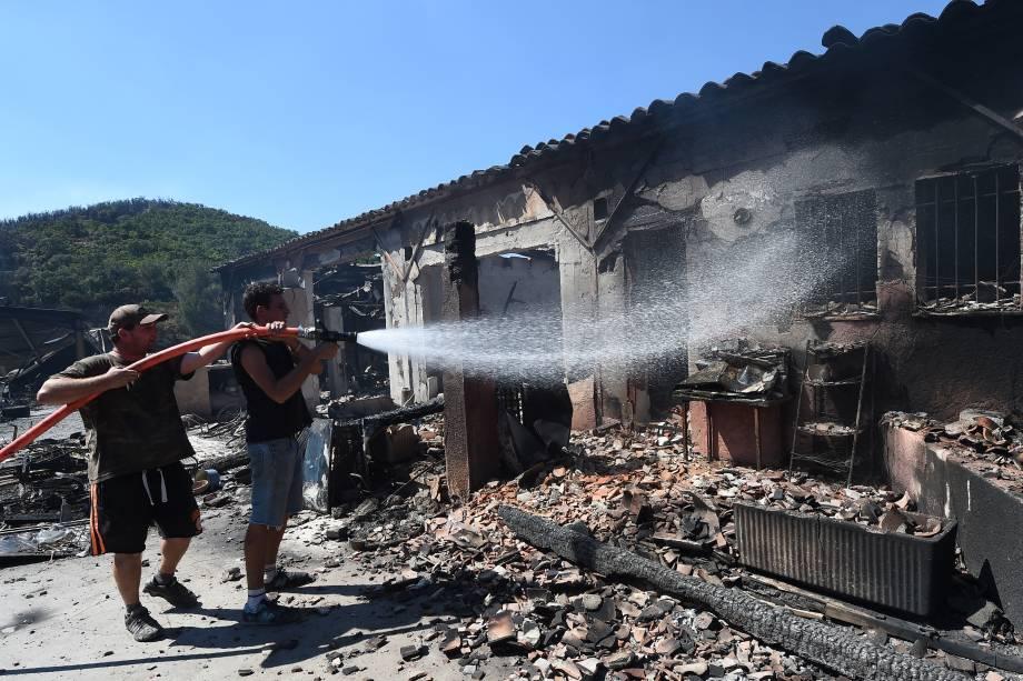 Proprietários de uma empresa de acampamento e caravanismo tentam extinguir as chamas do incêndio em seus edifícios em Bormes-les-Mimosas, na França