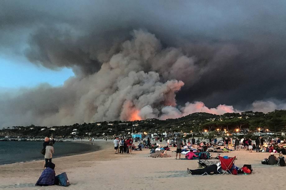 Pessoas que evacuaram suas casas se refugiam na praia e olham para o incêndio que queima a floresta em Bormes-les-Mimosas, no sul da França