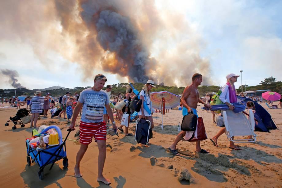 Banhistas deixam a praia em Bormes-les-Mimosas, no departamento de Var, enquanto a fumaça do incêndio florestal toma conta do céu na França