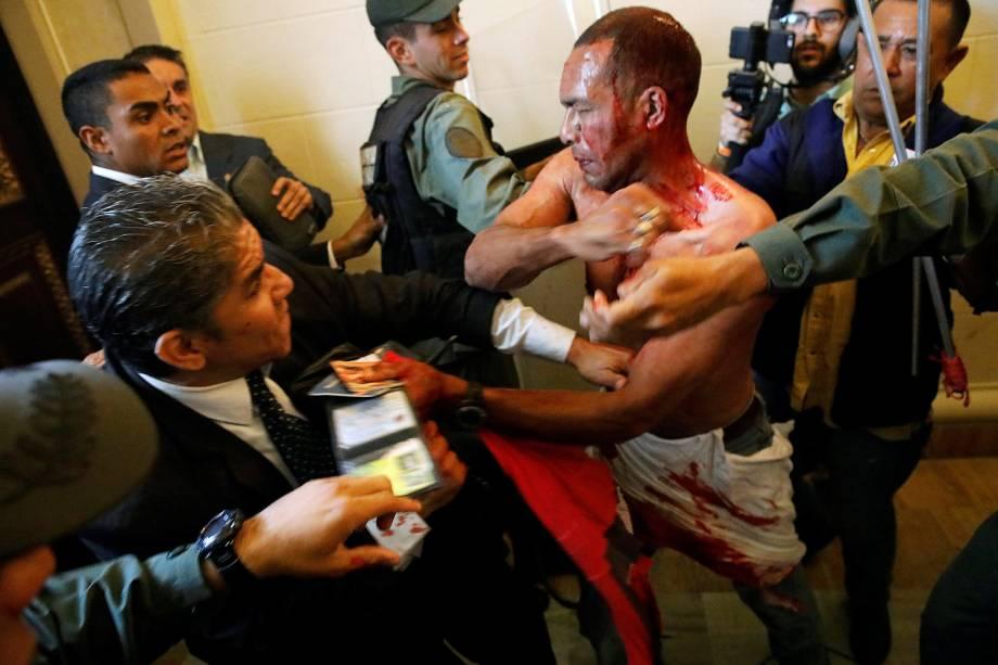 Homem coberto de sangue tenta deixar a Assembleia Nacional da Venezuela, após um grupo de apoiadores do governo de Nicolas Maduro invadiram a sede do Legislativo, controlada pela oposição, em protesto durante uma sessão parlamentar - 05/07/2017