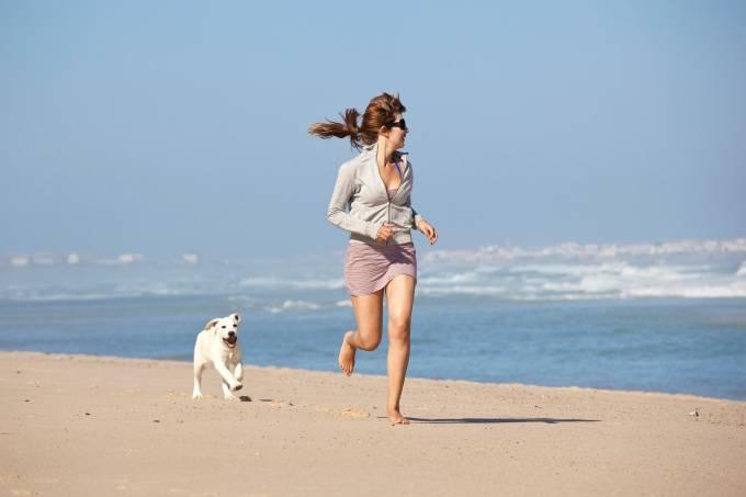 Mulher com cachorro na praia