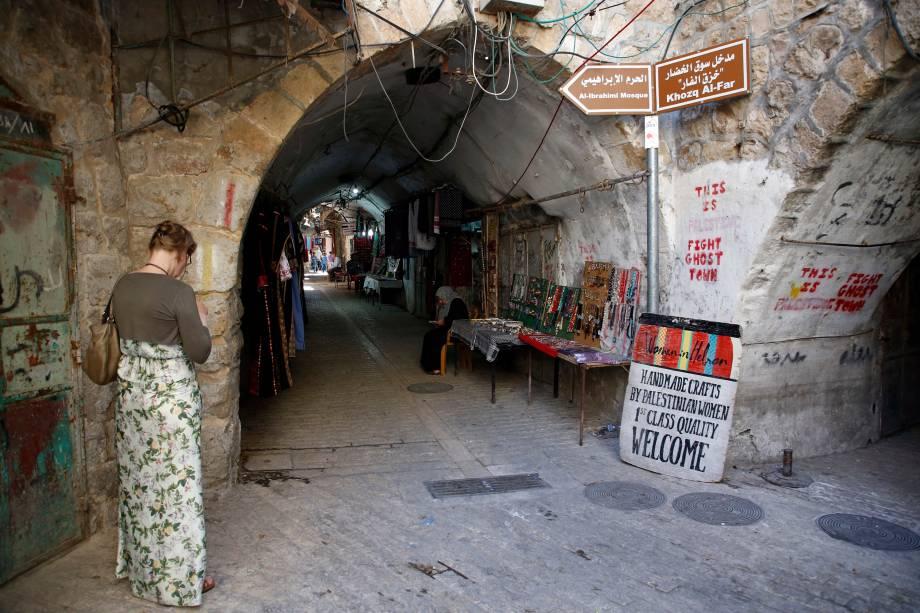 Mulher caminha no antigo mercado da cidade de Hebron, na Cisjordânia