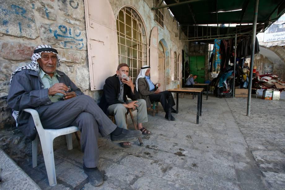Palestinos idosos fumam cigarros em um café na cidade velha de Hebron, na Cisjordânia