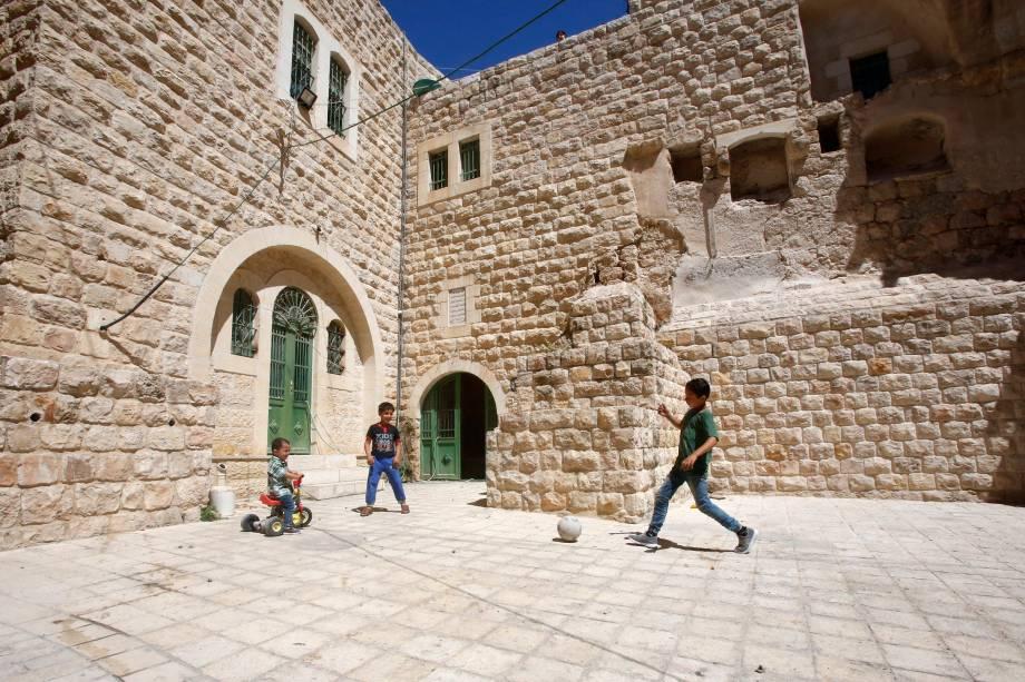 Crianças palestinas brincam com uma bola do lado de fora de sua casa na cidade velha de Hebron, na Cisjordânia