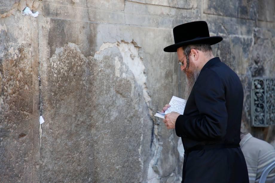 Judeu ultra-ortodoxo faz orações do lado de fora do túmulo dos Patriarcas ou da Mesquita de Ibrahimi, local sagrado para judeus e muçulmanos, na cidade de Hebron, na Cisjordânia