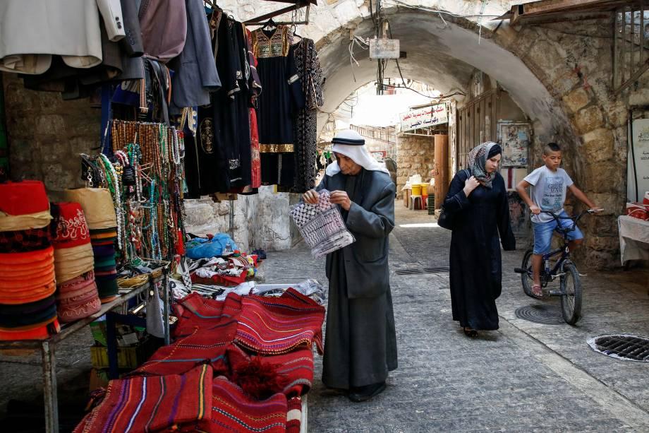 Palestinos transitam em beco no antigo mercado da cidade de Hebron, na Cisjordânia