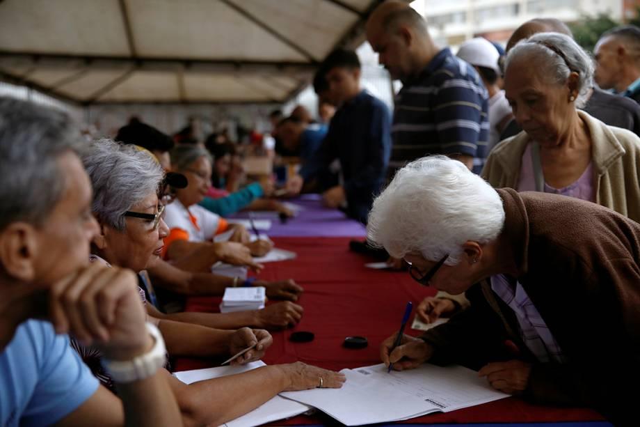 Mulher assina documento de plebiscito que vota contra o presidente Nicolas Maduro em Caracas, na Venezuela - 16/07/2017