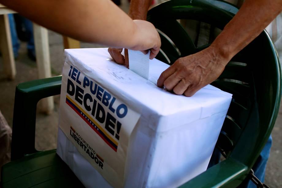 Pessoas depositam voto em urna durante plebiscito que vota contra o presidente Nicolas Maduro, em Caracas, na Venezuela - 16/07/2017