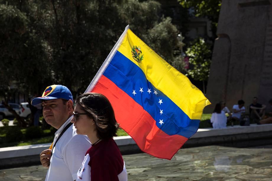 Casal caminha com bandeira da Venezuela como forma de protesto contra o presidente Nicolás Maduro - 16/07/2017