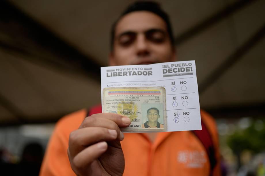 Eleitor exibe seu voto antes de depositá-lo em urna, durante plebiscito não-oficial organizado contra o presidente Nicolás Maduro - 16/07/2017