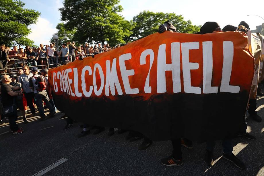 Manifestantes levantam cartazes para protestar contra a conferência do G20, em que líderes das maiores economias do mundo se reúnem para discutir assuntos como economia, política, meio ambiente, acordos de paz etc. - 06/07/2017
